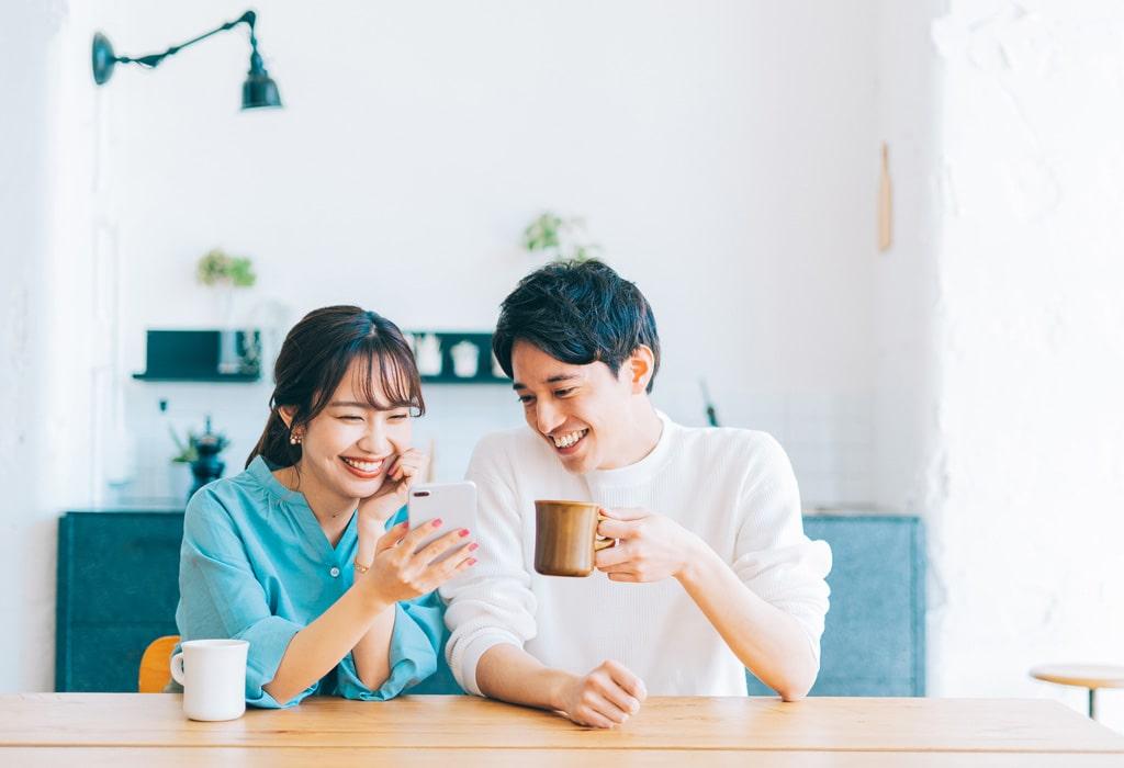 スマートフォンを寄り添うように見る若い夫婦